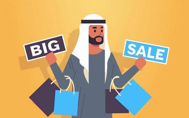 Hombre árabe con compras y pancartas de gran venta cliente de chico árabe con bolsas de compras oferta especial concepto de descuento de vacaciones retrato plano horizontal