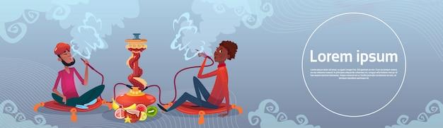 Hombre árabe fumando pipa de narguile sentado en el suelo