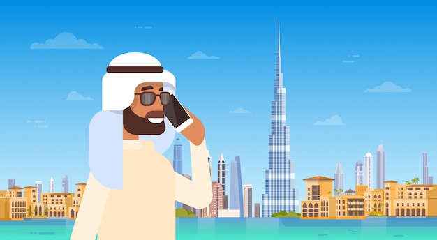 Hombre árabe hablando por teléfono celular llamada de teléfono inteligente sobre el panorama del horizonte de dubai, edificios urbanos de edificios modernos