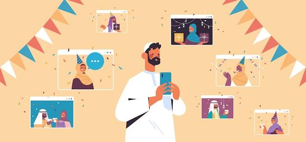 Hombre árabe que celebra la fiesta de cumpleaños en línea durante la reunión virtual con amigos árabes en la ilustración horizontal del concepto de autoaislamiento de celebración de ventanas de navegador web