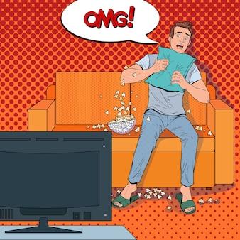 Hombre de arte pop viendo una película de terror en casa. chico sorprendido mira la película en el sofá con palomitas de maíz.