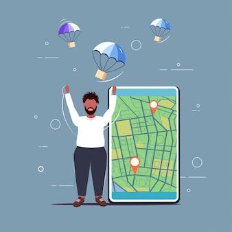 Hombre atrapando la caja de paquetería cayendo con paracaídas desde el cielo transporte envío concepto de servicio de entrega de correo aéreo chico afroamericano usando la aplicación móvil mapa de la ciudad con etiquetas geo
