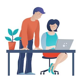 Hombre ayudando a la joven a trabajar en la computadora en la oficina