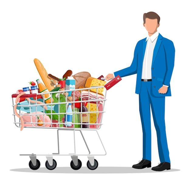 Hombre con carrito de compras lleno de productos frescos.