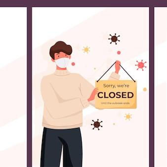 Hombre colgando un letrero cerrado