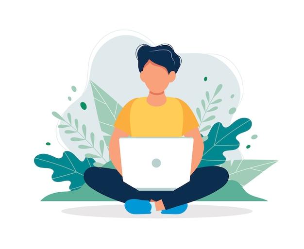 Hombre con la computadora portátil que se sienta en naturaleza y hojas.