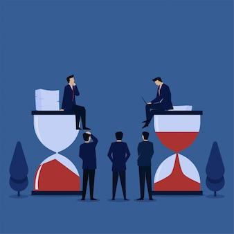 El hombre del concepto del ejemplo plano del negocio se sienta sobre el tiempo de la arena piensa y trabaja la metáfora del trabajador eficaz