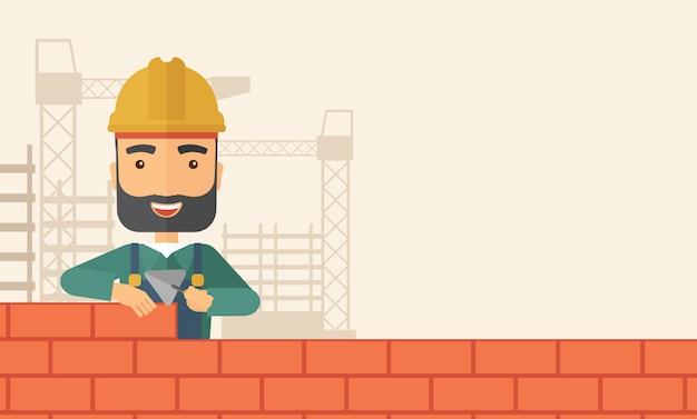 El hombre constructor está construyendo una pared de ladrillos.