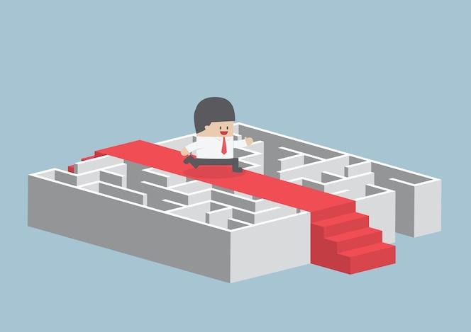 Hombre de negocios que se ejecuta en la alfombra roja sobre el laberinto