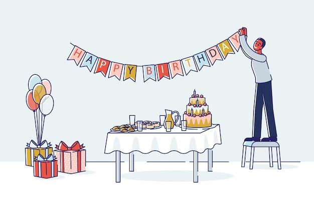 El hombre decora la habitación para la celebración de cumpleaños colgando guirnalda de vacaciones sobre la mesa con pastel.