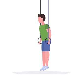 Hombre deportivo haciendo ejercicios de inmersiones de anillo con anillos de gimnasia tipo entrenamiento en gimnasio cardio crossfit entrenamiento estilo de vida saludable concepto fondo blanco longitud completa