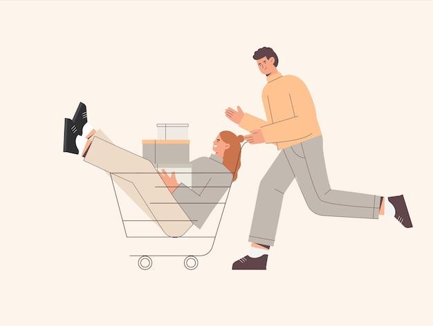 Hombre empuja el carrito de la compra con una mujer sosteniendo cajas o presenta paquetes con compras