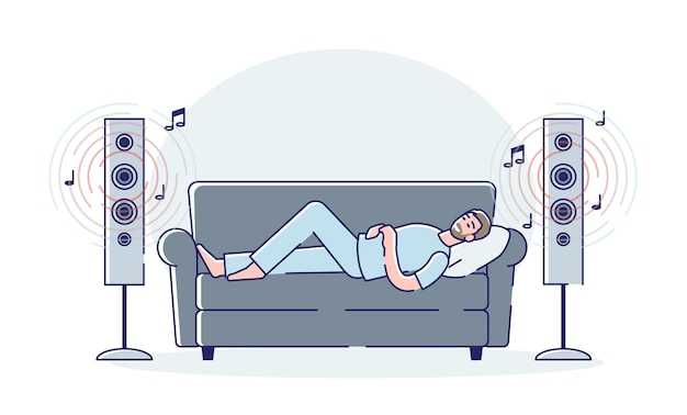 El hombre escucha música de los altavoces de sonido modernos en voz alta acostado en el autocar en casa