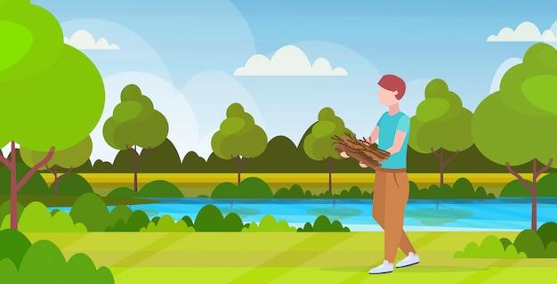 Hombre excursionista con leña para fogata senderismo camping concepto viajero en caminata hermosa naturaleza paisaje fondo plano horizontal horizontal de longitud completa