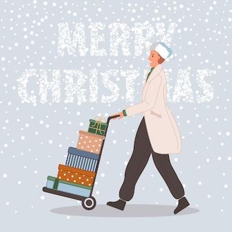 Hombre feliz con regalos de navidad en carretilla elevadora macho vistiendo gorro de papá noel sobre fondo de nieve