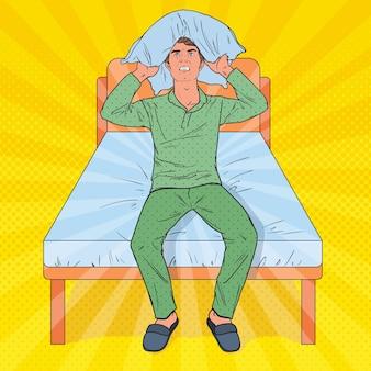 Hombre frustrado de arte pop cerrando las orejas con almohada. situación estresante de la mañana. guy sufre de insomnio.