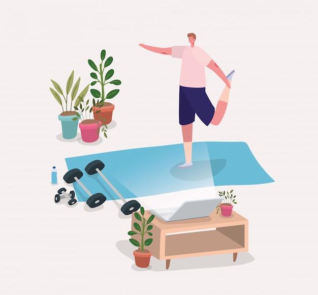 Hombre haciendo yoga en la estera delante del portátil
