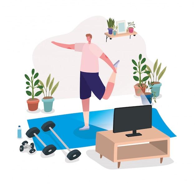 Hombre haciendo yoga en la estera delante de la televisión