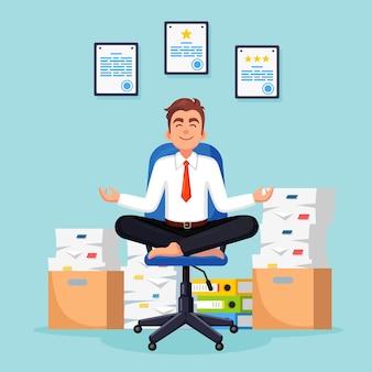Hombre haciendo yoga, sentado en la silla de oficina. pila de papel, empleado estresado ocupado con documentos