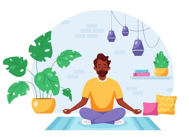 Hombre indio meditando en posición de loto en interior acogedor