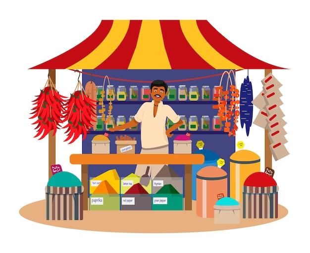 Hombre indio vendiendo especias en la tienda de la calle