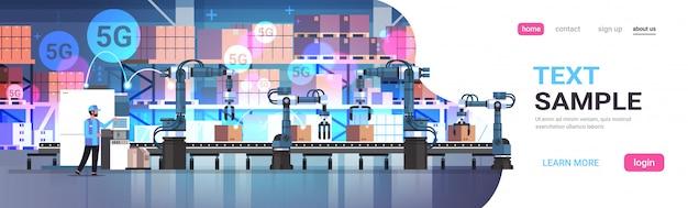 Hombre ingeniero que controla la línea de la cinta transportadora manos robóticas producción de automatización de fábrica