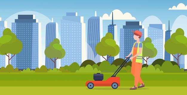Hombre jardinero en uniforme de corte de césped con cortadora de césped concepto de jardinería paisaje urbano moderno fondo plano de longitud completa horizontal