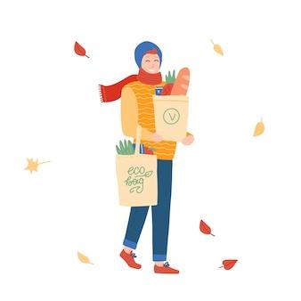 Hombre joven con bolsas de papel reutilizables de compras de comestibles. personaje de dibujos animados comprando cosas en la tienda. chico con ropa abrigada de otoño. ilustración plana.