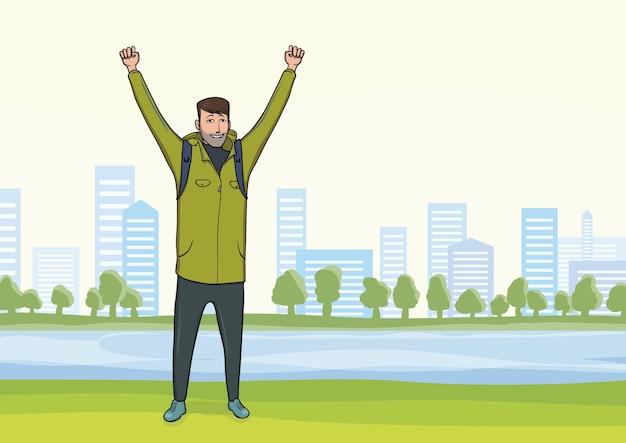 Hombre joven feliz en el paseo matutino en el parque de la ciudad. un turista con las manos en alto, gesto de acierto a goles. .