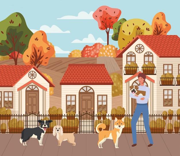 Hombre joven con mascotas perros lindos en la escena de la ciudad de otoño