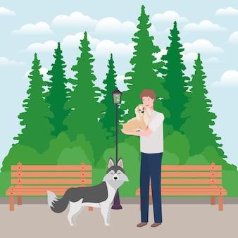 Hombre joven con mascotas perros lindos en el parque