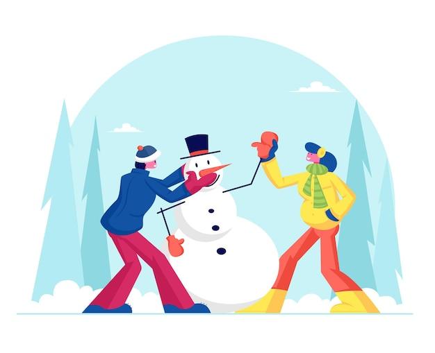 Hombre joven y mujer en ropa de abrigo haciendo divertido muñeco de nieve sobre fondo de paisaje nevado. ilustración plana de dibujos animados