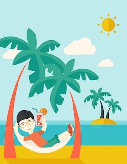 Hombre joven en la playa relajante y beber cócteles.