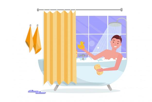 Hombre joven que toma la bañera con espuma de burbujas.