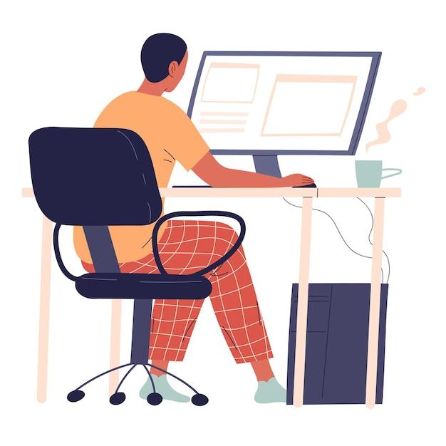 El hombre joven se sienta en su escritorio y trabaja en su computadora.