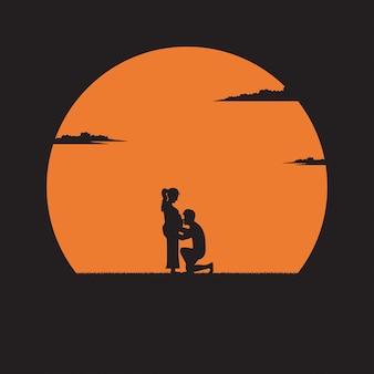 Hombre joven de la silueta que besa el vientre de su esposa embarazada en fondo de la puesta del sol