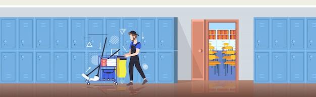 Hombre limpiador empujando el carrito con suministros conserje masculino en uniforme