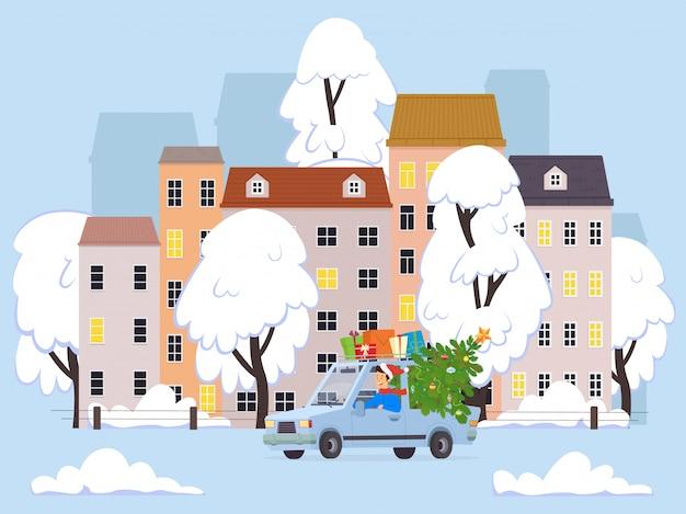 El hombre lleva un automóvil y presenta un árbol de navidad a lo largo de la calle principal de la ciudad.
