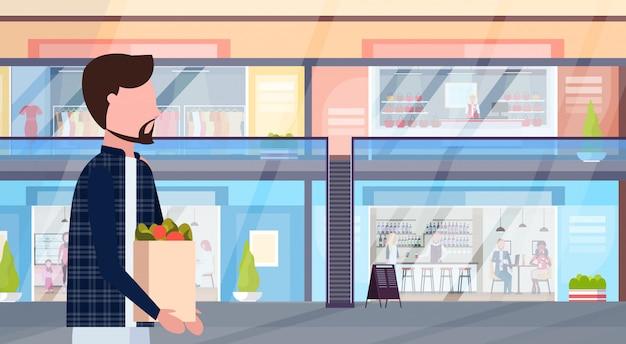 Hombre llevando bolsa de compras con comestibles personaje de dibujos animados masculino caminando moderno centro comercial con tiendas de ropa y cafeterías supermercado interior horizontal retrato plano