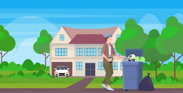 Hombre mendigo sosteniendo una botella de alcohol vagabundo buscando comida y ropa en el bote de basura en la calle desempleados desempleados concepto de pobreza pobreza cabaña edificio campo fondo completo