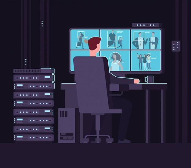 Hombre mirando la cámara de vigilancia en el monitor en la oscura sala de control.