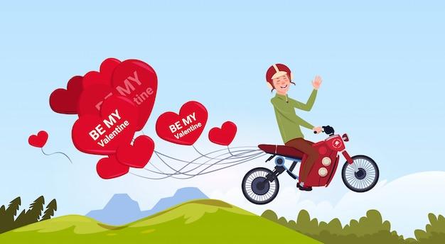 Hombre montando bicicleta de motor con globos de aire en forma de corazón concepto de feliz día de san valentín