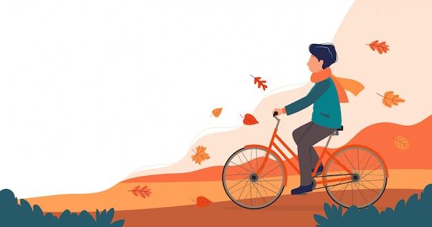 Hombre montando bicicleta en el parque en otoño.
