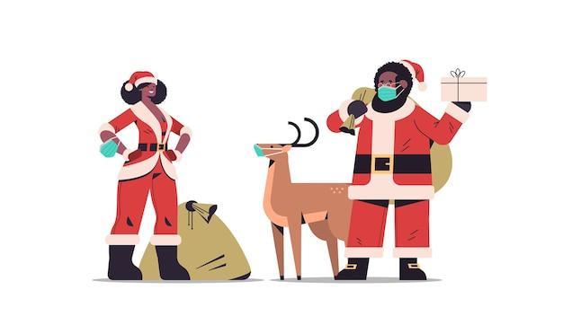 Hombre mujer afroamericana en máscaras vistiendo trajes de santa claus feliz año nuevo feliz navidad celebración navideña concepto ilustración vectorial horizontal de longitud completa
