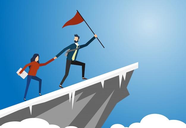 Un hombre y una mujer con una bandera roja se dan la mano y suben al acantilado alto con nieve en el suelo con cielo azul.