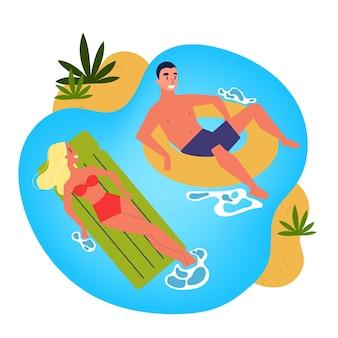 Hombre y mujer flotando en círculo inflable