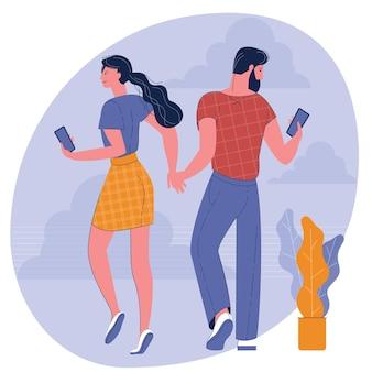Hombre y mujer joven caminando con sus teléfonos inteligentes tomados de la mano