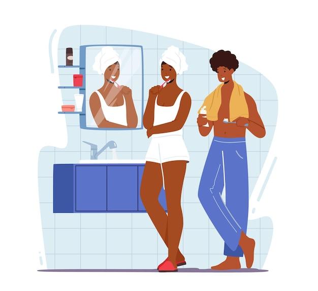 Hombre y mujer joven de pie delante del espejo en el baño y cepillarse los dientes después del baño
