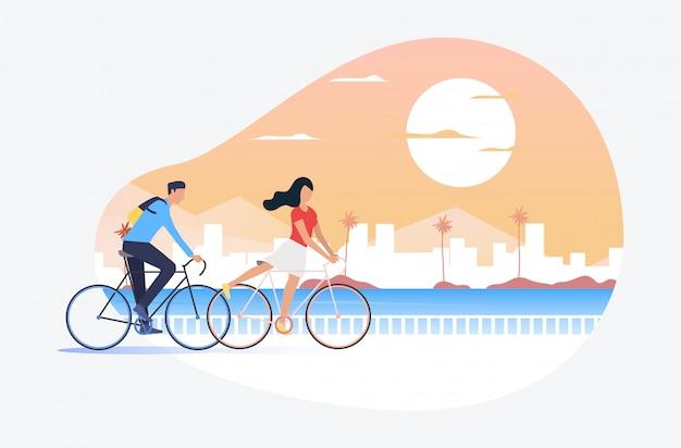 Hombre y mujer montando bicicletas, sol y paisaje urbano en el fondo
