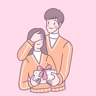 Un hombre con una mujer con los ojos vendados se sorprende con una caja de regalo.